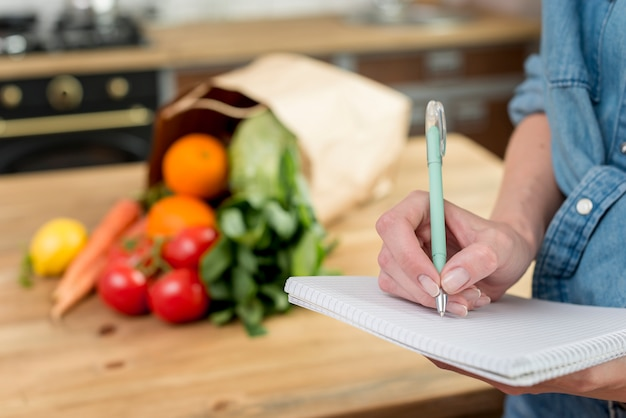 Person writing a recipe in the notebook Free Photo