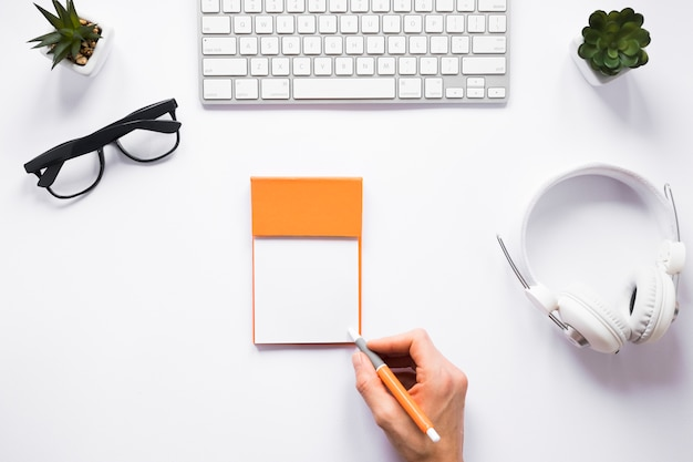A person writing on sticky notes with pen on white workspace Free Photo