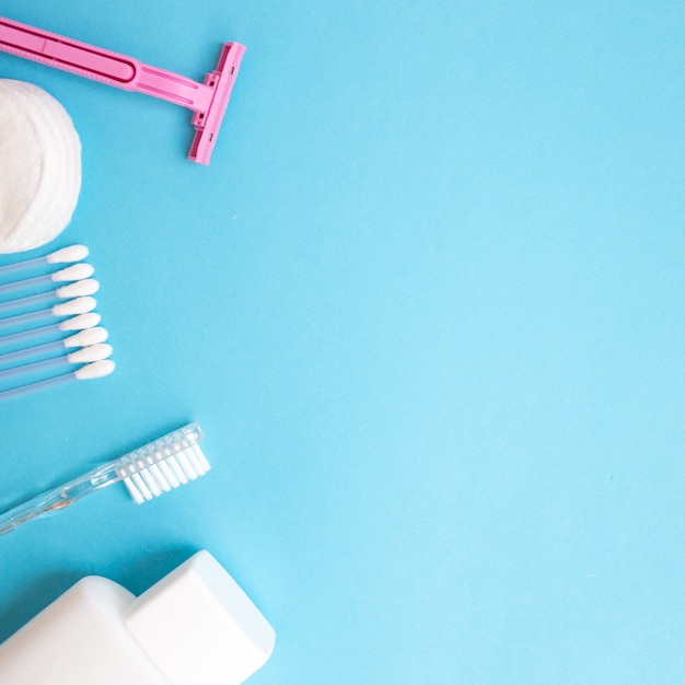 Personal care products. white bottle, razor, ear sticks, cotton pads, toothbrush on blue b Premium Photo