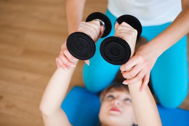 체육관에서 아령으로 운동을하는 여자를 돕는 개인 코치. 프리미엄 사진