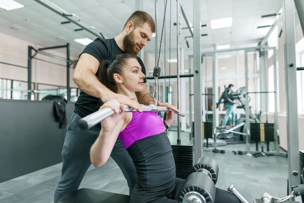 Personal fitness trainer coaching and helping client woman Premium Photo