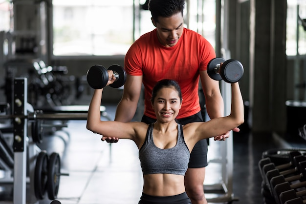 Personal trainer coaching dumbbell to woman Premium Photo