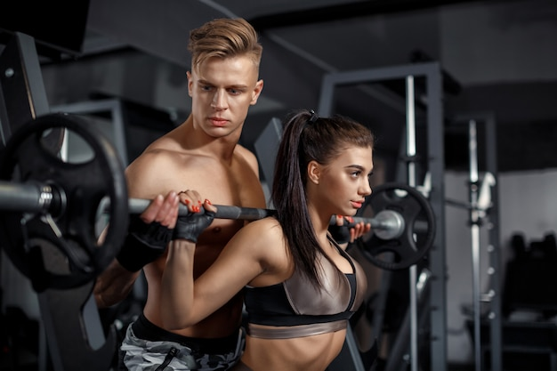 Personal trainer model helps woman model to lift the barbell in the gym Premium Photo