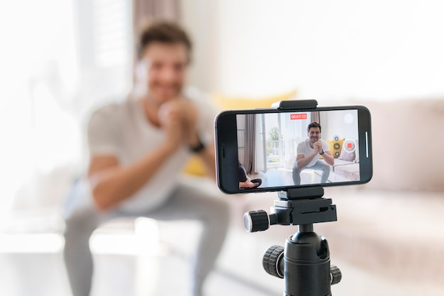 Personal trainer recording exercises at home Free Photo