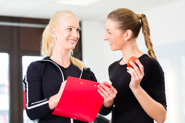 Personal trainer with woman in fitness studio Premium Photo