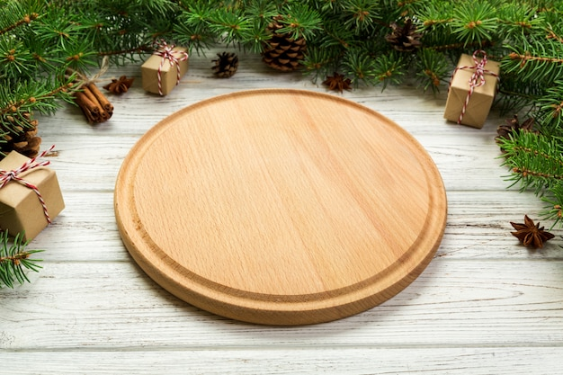 Perspective view. empty wood round plate on wooden christmas board. holiday dinner dish concept with new year decor Premium Photo