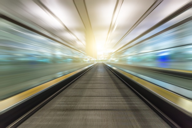 Perspective wide angle black and white view of modern light blue illuminated and spacious high-speed moving escalator with fast blurred trail of handrail in vanishing traffic motion Premium Photo