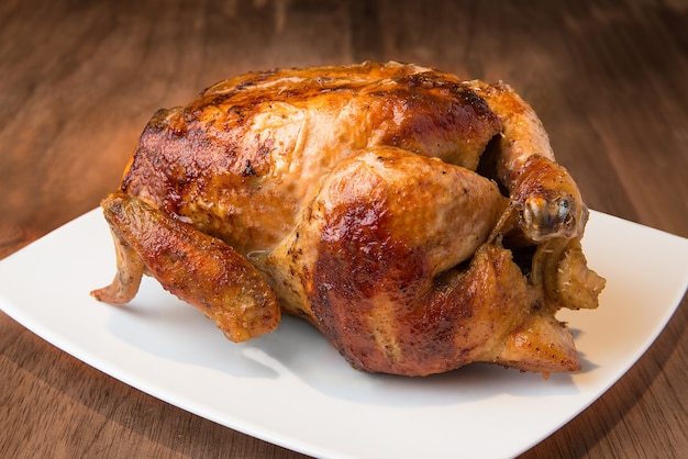 Peruvian food delicious whole grilled chicken on wood texture Premium Photo