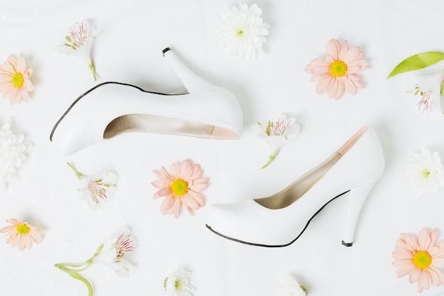 Peruvian lily and gerbera flowers with wedding high heels on white backdrop Free Photo