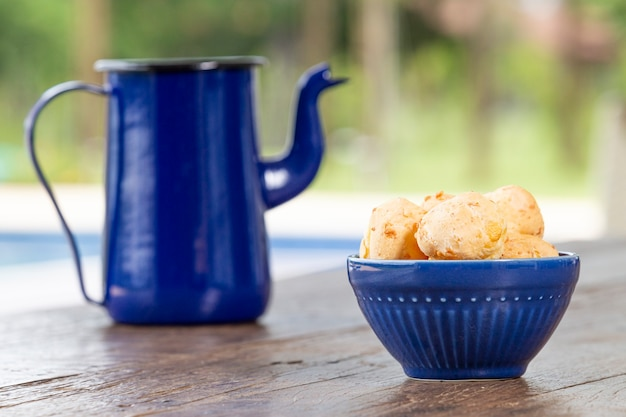 Pestic brazilian, cheese bread. on a rustic table. and the bottom is a blue coffee pot. Premium Photo