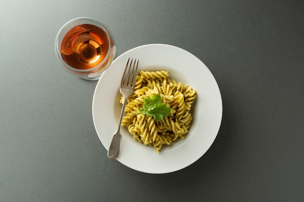 Pesto pasta and rose wine glass in white plate over gray background. italian food. Premium Photo