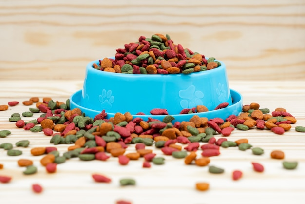 Pet bowl with dry food on wooden table Premium Photo