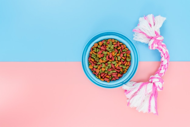 Pet food and toy with copy space on color background Premium Photo
