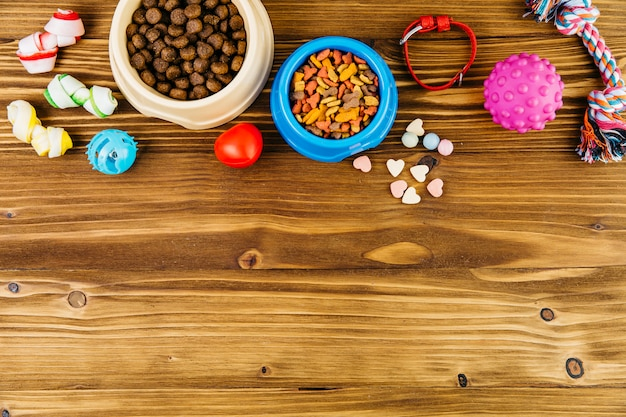 Pet food and toys on wooden surface Free Photo