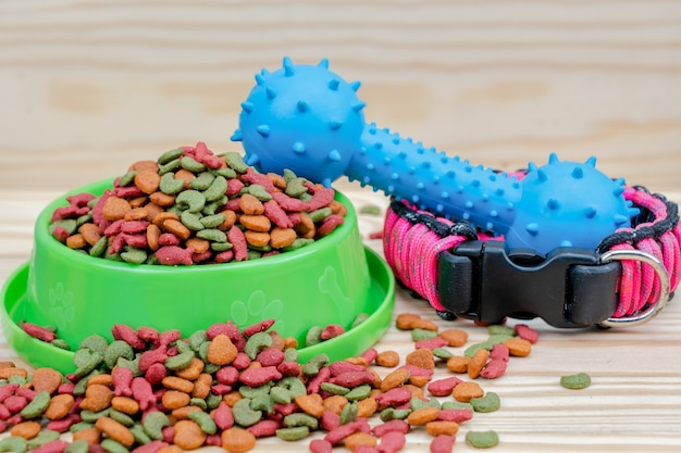 Pet food with rubber toy on wooden background Premium Photo