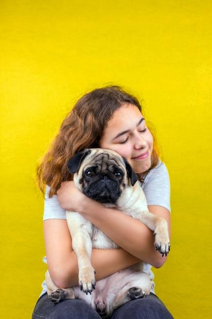 ペット愛。カーリーティーンエイジャーの女の子は愛で彼女の悲しいパグ犬を抱擁します。 Premium写真