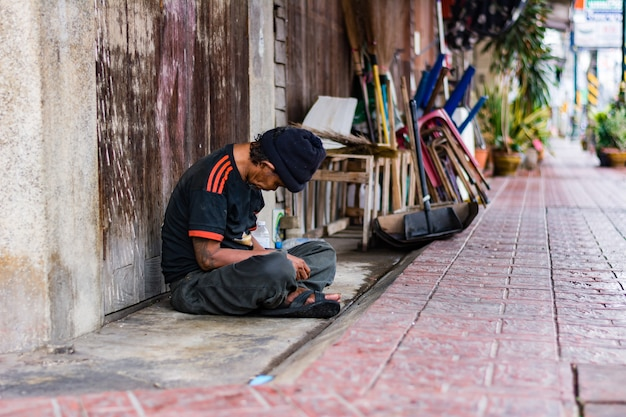 Petchburee,thailand – 27 feb 2018: beggar man sleeping beside sidewalk for money on the street Premium Photo