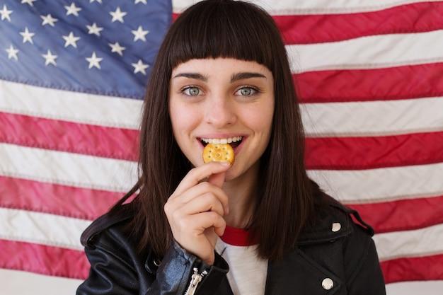 トレンディな流行に敏感な服装の小柄な女性またはティーンエイジャーは、カリカリのピーナッツバタークッキークラッカー、アメリカの国旗の典型的な伝統的なアメリカのスナックでポーズを食べます 無料写真