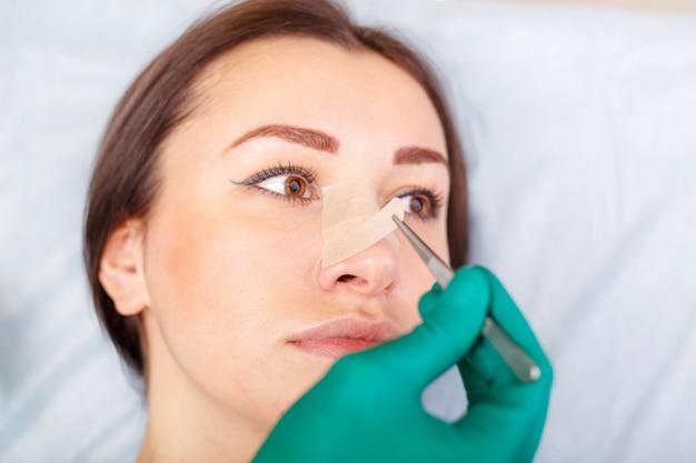 医者は女性の顔、整形手術前のまぶた、眼pha形成をチェックします。 Premium写真