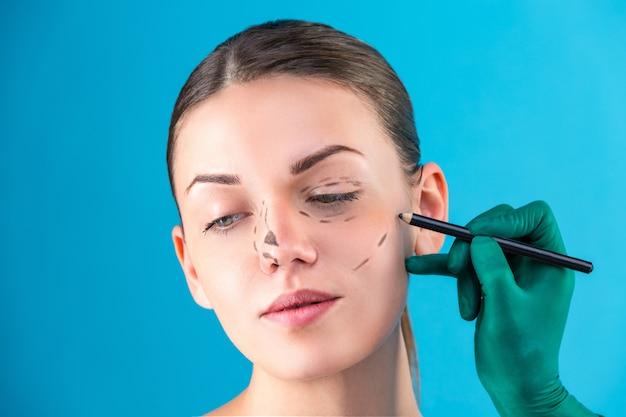 オフィスで女性のクライアントを調べる美容整形外科医。医師はマーカー、整形手術前のまぶた、眼pha形成術で線を引きます。女性の顔に触れる外科医や美容師の手。鼻形成術 Premium写真