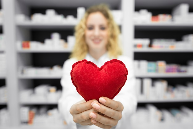 Pharmacist in drug store holding heart Free Photo