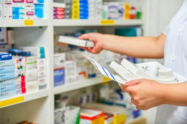 Фармацевт заполняет рецепт в аптечной аптеке Premium Фотографии