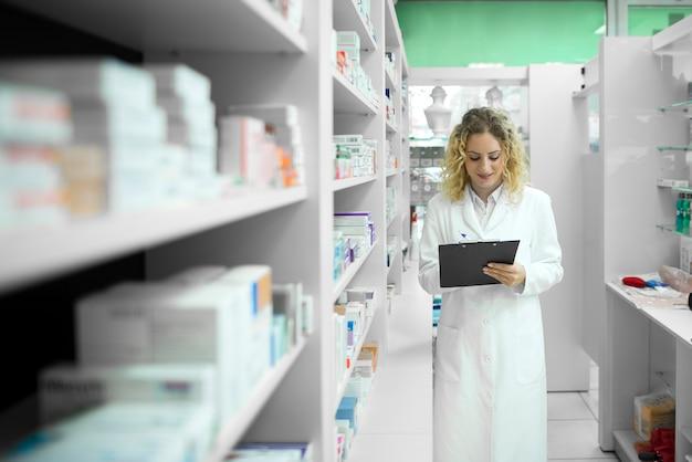 Аптекарь в белой форме идет мимо полки с лекарствами и проверяет инвентарь Бесплатные Фотографии
