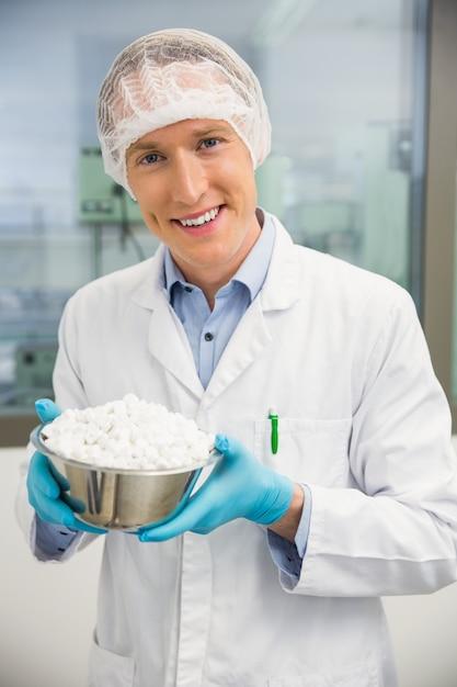 Pharmacist looking at bowl of pills Premium Photo