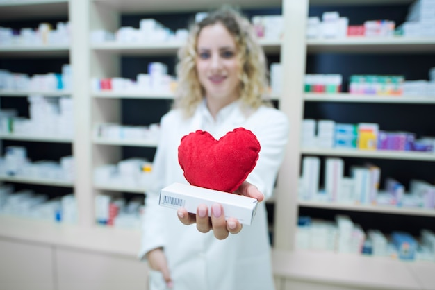 Pharmacist in white uniform holding medicines for cardiovascular disease Free Photo