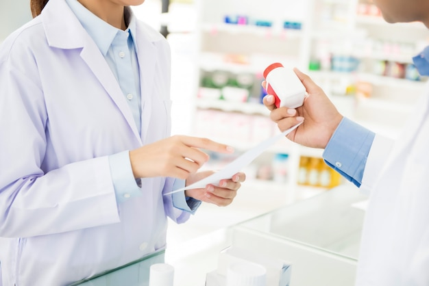 Pharmacists showing medicine bottle and discussing prescription drug in a pharmacy. Premium Photo