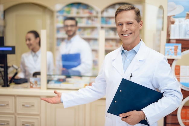 Pharmacists stand in pharmacy and hold a folder with papers. Premium Photo