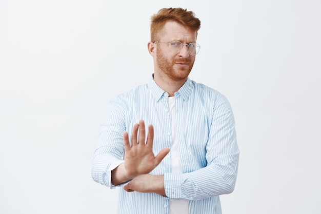Phew, no thanks, i pass. displeased unimpressed and uninterested handsome mature redhead man with beard, turning away and pulling palm towards in no gesture, refusing or declining offer Free Photo
