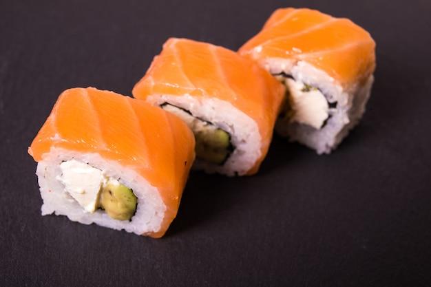 I rotoli di sushi di filadelfia california si trovano sul piatto ceramico nero Foto Gratuite