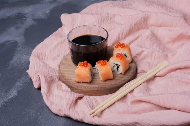 ピンクのテーブルクロスにフィラデルフィアの巻き寿司、醤油、箸。 無料写真