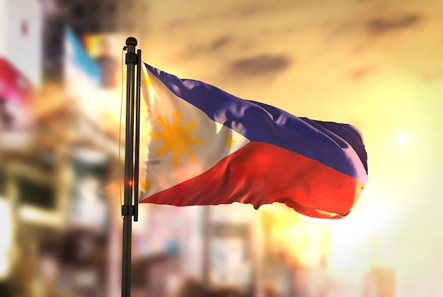 日の出のバックライトで都市がぼやけた背景に対してフィリピンの国旗 Premium写真
