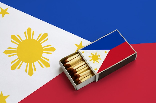 Philippines flag  is shown in an open matchbox, which is filled with matches and lies on a large flag Premium Photo
