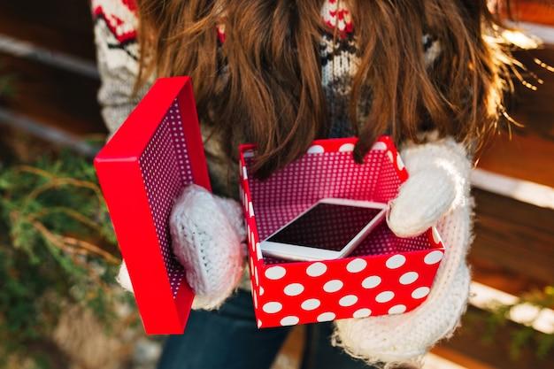 かわいい女の子の手袋を保持している赤いボックスにクリスマスプレゼントとして電話。 無料写真