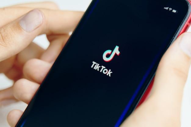 Phone in hand. tik tok application icon on phone. close-up. Premium Photo