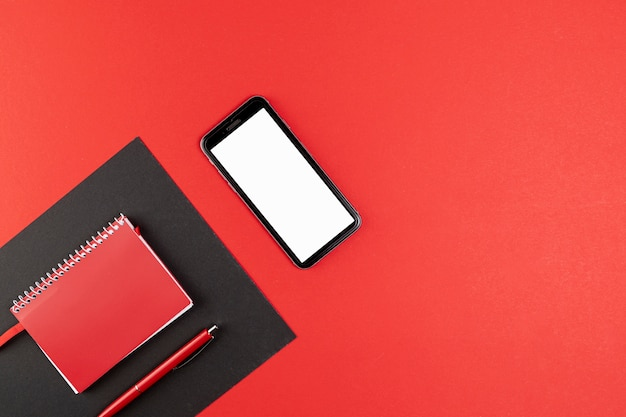 Phone mock up next to red notebook Free Photo