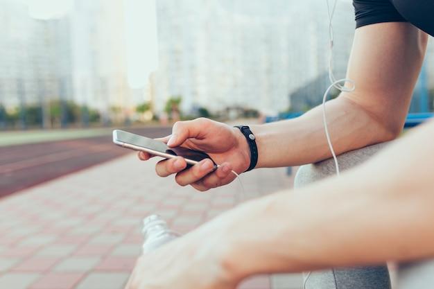 Telefono in mano muscolare del ragazzo seduto in città la mattina. tiene la bottiglia d'acqua e le cuffie. Foto Gratuite