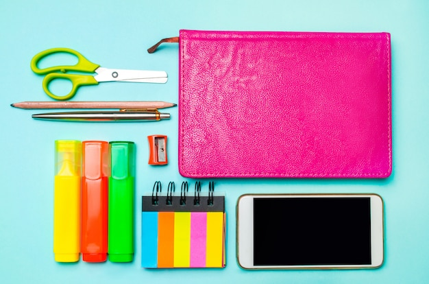 Phone, notebook, pen, scissors, colored markers, pencil, sticky stickers Premium Photo