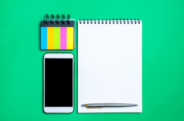 Phone, notebook, pen and sticky stickers on the school desk Premium Photo
