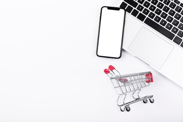Phone on top of laptop with shopping cart Premium Photo