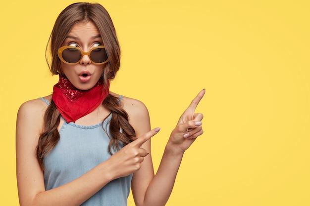 La foto di hipster bruna stupita ha un'espressione stupita, indica con l'indice nell'angolo in alto a destra Foto Gratuite
