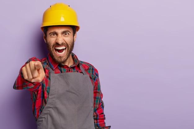 La foto del caposquadra infastidito indica, urla di rimprovero, urla con rabbia al collega, indossa casco, camicia e grembiule gialli. il costruttore irritato risolve il problema sul lavoro Foto Gratuite