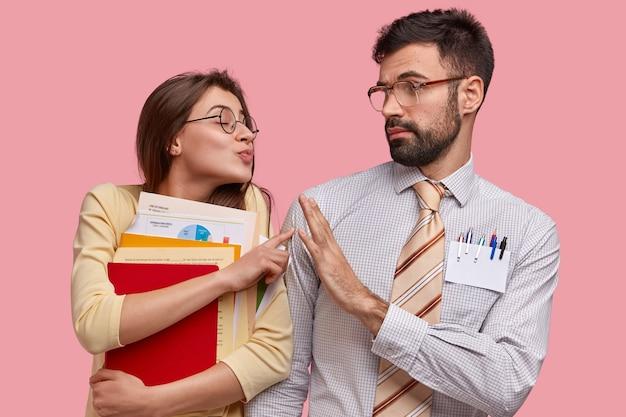 Foto di attraente donna premurosa vuole baciare un bel ragazzo che cerca di fermarla, fa il gesto di rifiuto Foto Gratuite