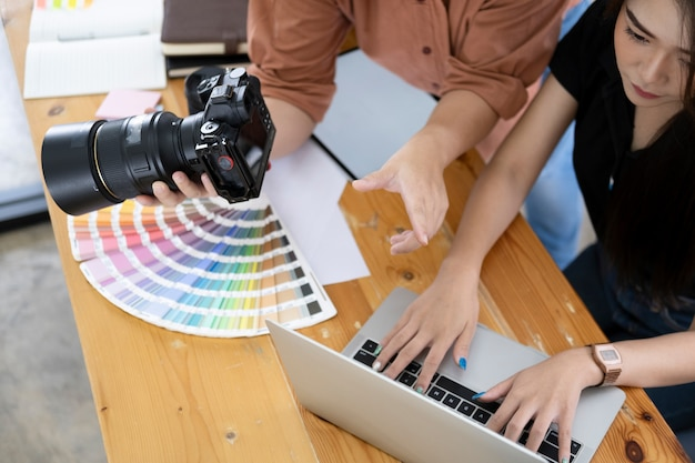 Photo artist and graphic desginer selecting pictures from camera. Premium Photo