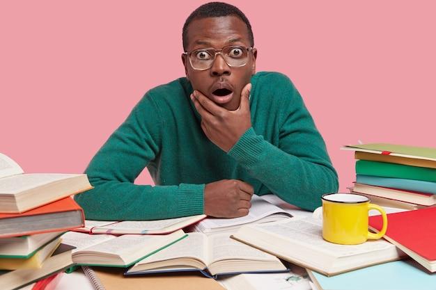 La foto del giovane nero stupito tiene il mento, fissa incredulo, ha molti libri aperti intorno al tavolo Foto Gratuite