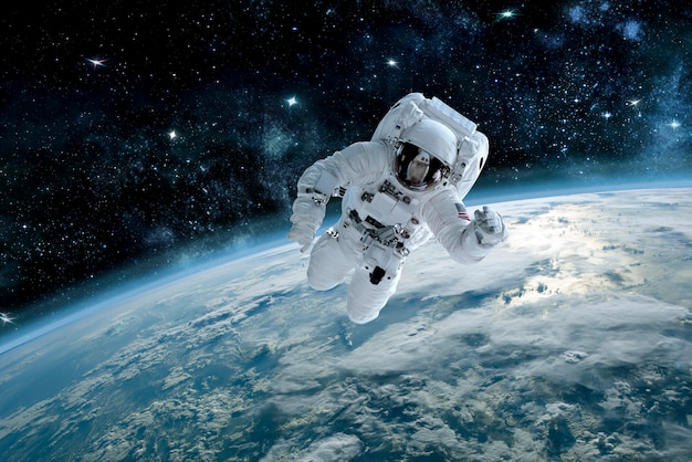 Photo of astronaut in space, in background planet earth. elements of this image furnished Premium Photo
