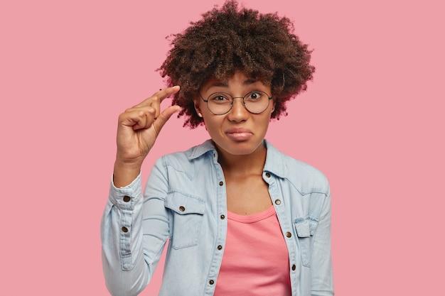 La foto di una giovane donna attraente con un taglio di capelli afro mostra qualcosa di molto piccolo o minuscolo, gesticola con la mano, ha la pelle scura, vestita con una giacca di jeans, isolata su un muro rosa. è troppo piccolo Foto Gratuite